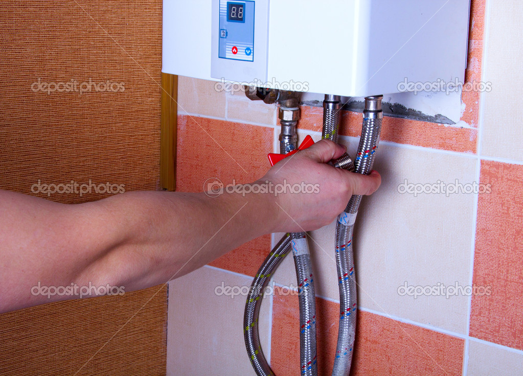 man tests the reliability of fastening of pipes in water heater
